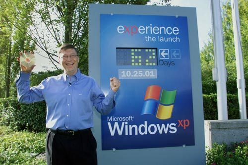 "Microsoft then-CEO Bill Gates poses with Windows XP ""gold"" disc. [Microsoft]"