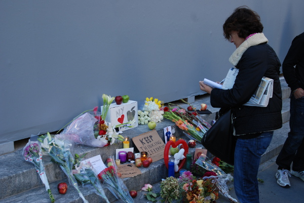 A woman writes, perhaps a message, before the small shrine of flowers outside Apple Store Fifth Avenue on Oct. 6, 2011.  [Tim Conneally]
