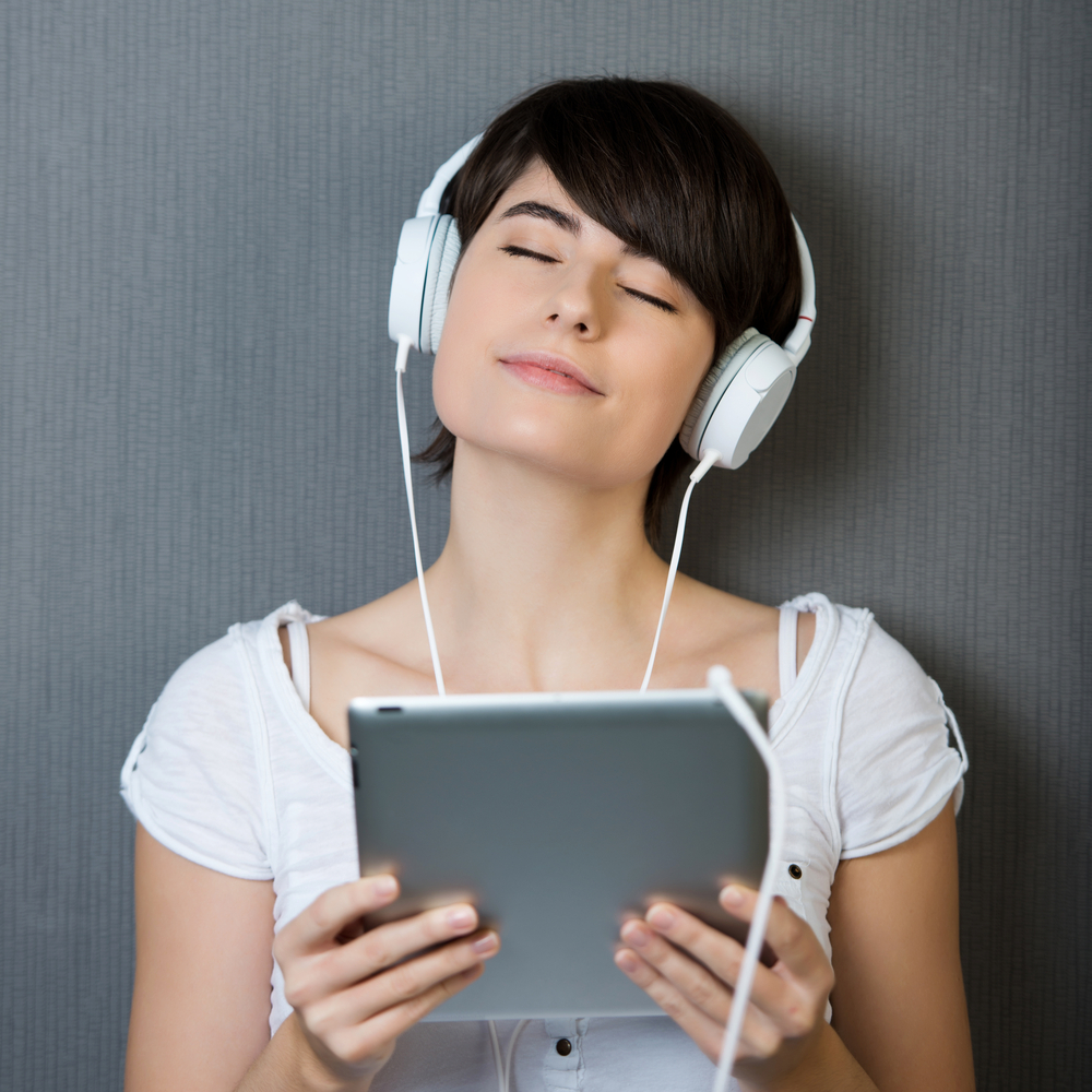woman listening to music on tablet