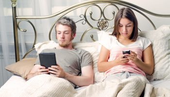couple in bed with phones