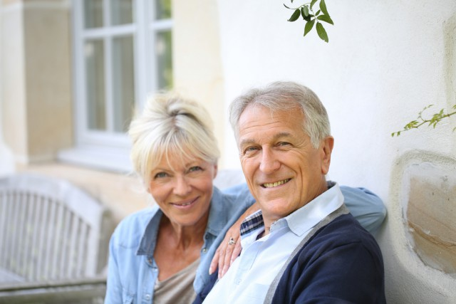 Elderly couple smiling sitting on a porch bench