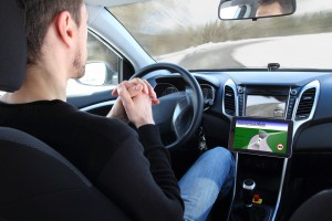 Man in a self-driving car, no hands on the steering wheel