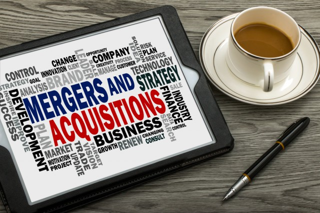 Mergers and acquisitions message displayed on a tablet, with a coffee cup and pen nearby