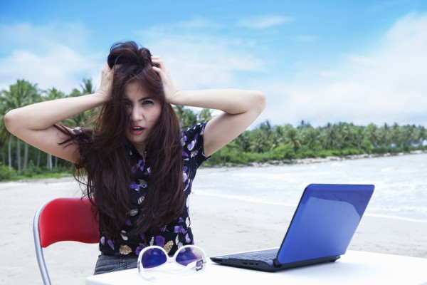 Unhappy laptop user on beach