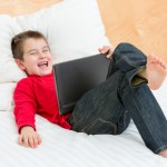 Boy laughing bed tablet laptop