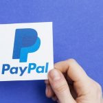 Hand holding a PayPal logo