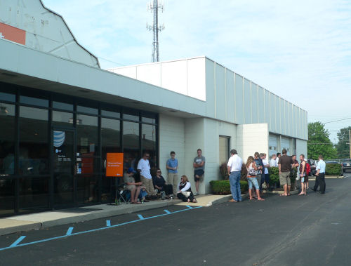 About two dozen people finally formed a line just after a sales clerk hauled out this orange sign.