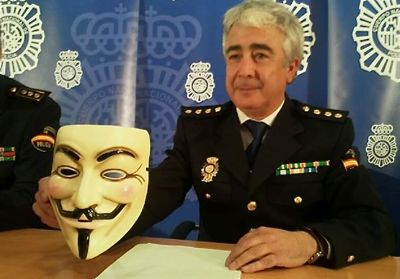 BIT commissioner Manuel Vazquez holds up the trademark Anonymous Guy Fawkes mask